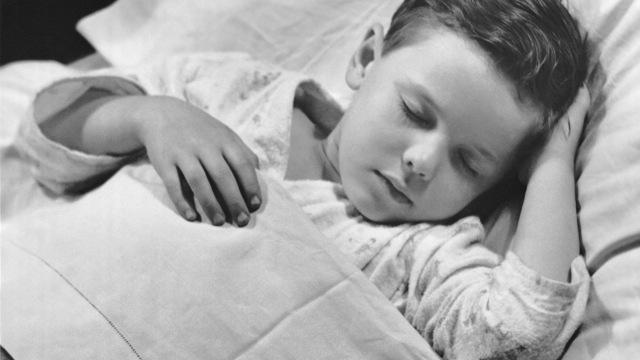 gutt i seng med sengevæting