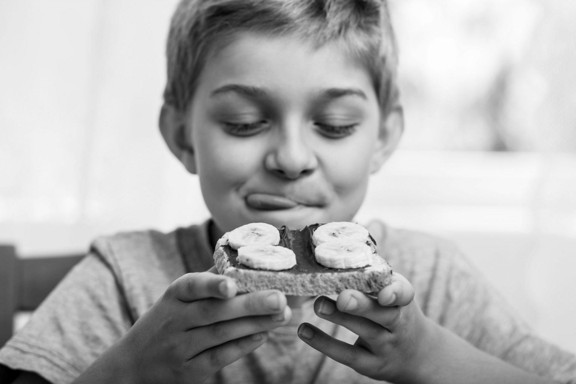 gutt spiser brødskive med nugatti og banan